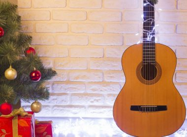 Guitar christmas background with holiday tree and gifts