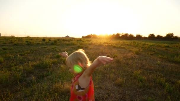 das Mädchen dreht sich im Sonnenuntergang auf dem Feld.