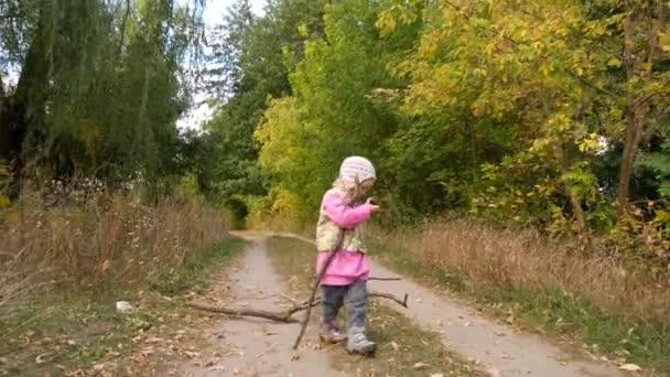 Ein Mädchen sammelt Brennholz im Wald. das Kind trägt Holz ans Feuer.