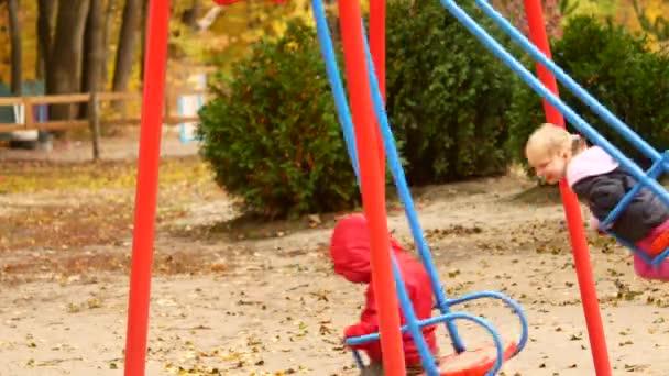 Dvě děti jezdit na houpačce. Podzimní park a dětské hřiště s houpačkou