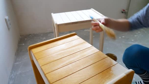 Holzwerkstatt. Anwendung von Schutzlack auf Holz.