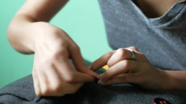 The seamstress sews a button on her clothes. Needlework and minor clothing repair
