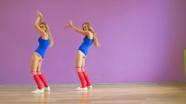 Vor dem Hintergrund einer lila Wand tanzen zwei Mädchen in blauen Badeanzügen. Mädchen im Disco-Stil tanzen sexy.
