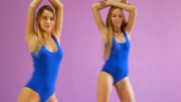 Dvě dívky v modrých plavkách tančit na pozadí fialové zdi. Dívky v disco stylu tančí sexy