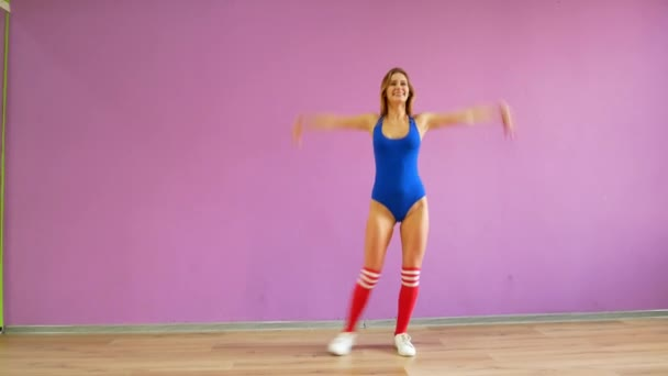 girls in blue bodysuits dance against the background of a purple