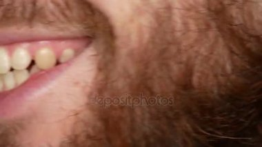 Close-up of a bearded man. He turns his head into a frame and smiles. The guys teeth are broken