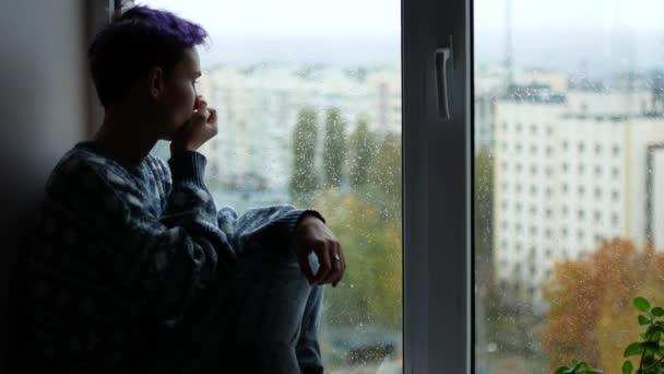 Žena má výtok z nosu. Mladá dívka sedí u okna, prší venku. Deprese
