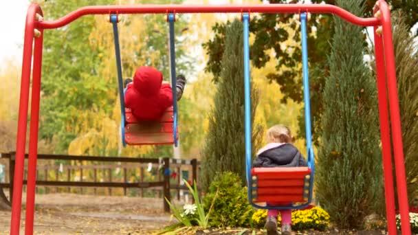 Zwei Kinder reiten auf einer Schaukel. Herbst Park und Kinder-Spielplatz mit Schaukel.