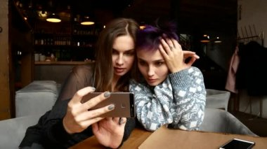 Two girlfriends are making selfies in a restaurant. Women are photographed in a cafe at the table