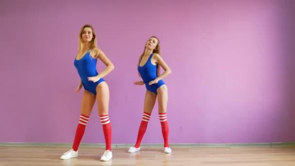 Two girls dance modern dances. Women in swimsuits and leg warmers