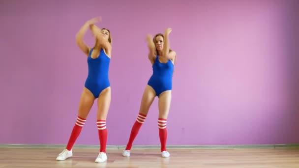 Dvě dívky tančí moderní tance. Ženy v plavkách a návleky