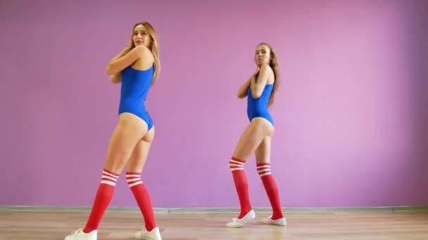 Due ragazze ballano danze moderne. Donne in costumi da bagno e ...