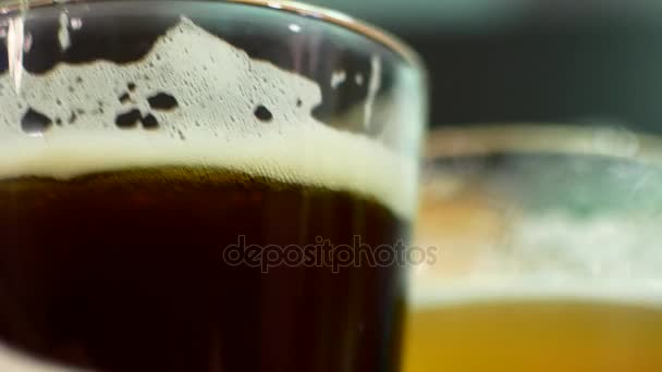 Sklo tmavé a světlé pivo close-up. IPA a loudal v pivní sklenice. Přátel pijí pivo v baru