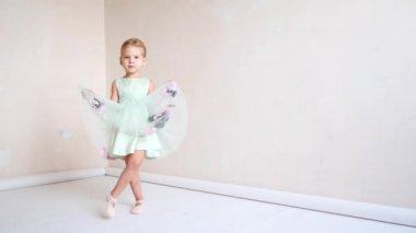 A cute girl is in her ballet uniform dancing