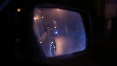 Wet car rear view mirror. Nighttime urban traffic