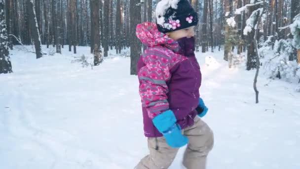 setzt sich das Mädchen in den Schlitten. Winterwald.