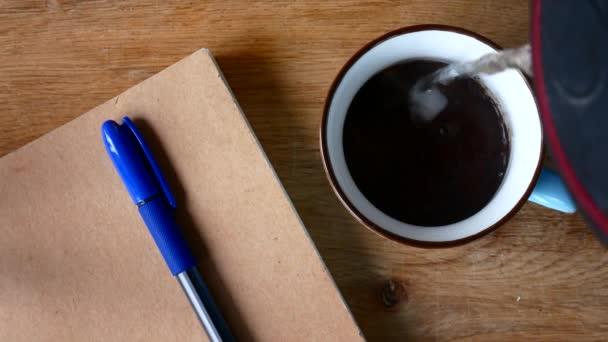 Egy csésze kávé és egy Jegyzetfüzet-val egy tollat. A koncepció a szabadúszó.