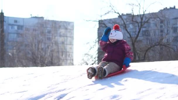 Kind auf einem Winterspaziergang. Ein Mädchen reitet von einer Schneerutsche auf einer Plastikplatte.