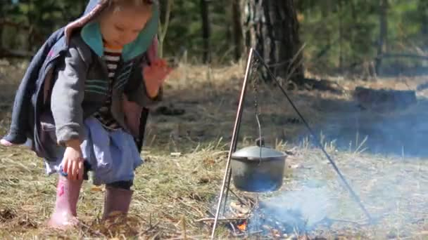 A little girl throws wood on the campfire. Independence and diligence