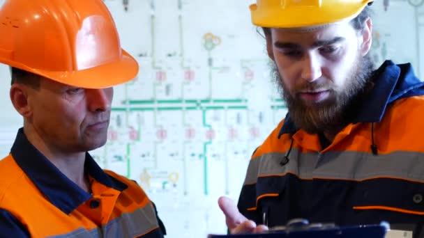 Dva inženýři v ochranné přilby spolupracovat v oblasti stavebnictví