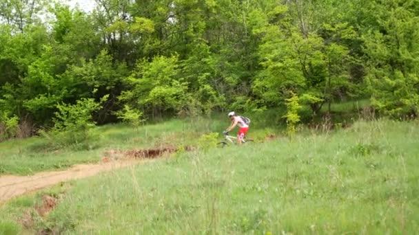 Mladý muž rychle jezdí na kole v oblasti zelené jarní krajinou podél cesty. Koncepce sportu mládeže