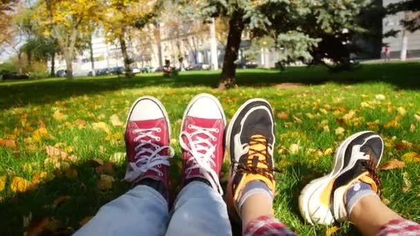 Rande v parku. Chlap a holka sedí na trávě na slunci. Vidíme jen jejich boty..