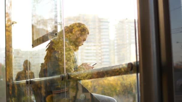Muž na zastávce městské hromadné dopravy čeká na autobus. Muž používá mobilní internet, zatímco čeká na transport