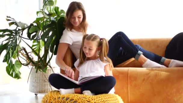 Matka a dcera čtou knihu, zatímco sedí na gauči. Máma ukazuje prstem na knihu