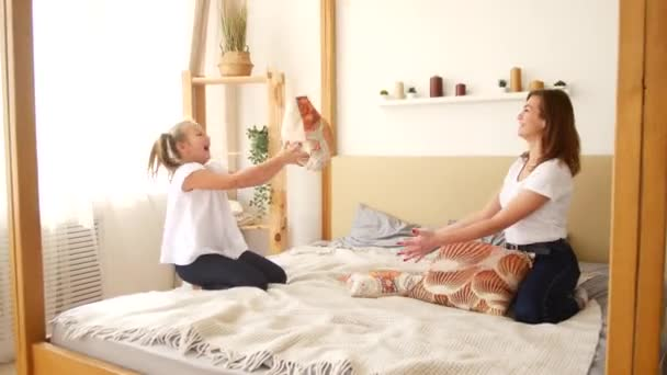 Mom and daughter throw pillows while sitting on the bed. Having fun and fooling around in the family circle