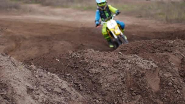 Motokrosové závody, motocykly na prašné dráze. V popředí trávy a půdy, účastníci soutěže v defokusu