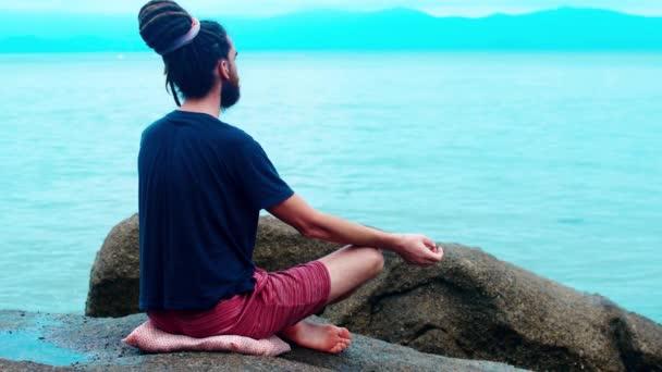 Muž medituje na kameni u moře. Lotosový chlápek s dredy