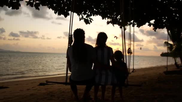 Happy family on vacation. Mom dad and baby ride on a swing and watch the sunset near the sea