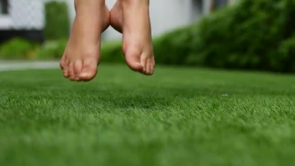 Nahé nohy na trávě. Zelená tráva v parku láká bosá
