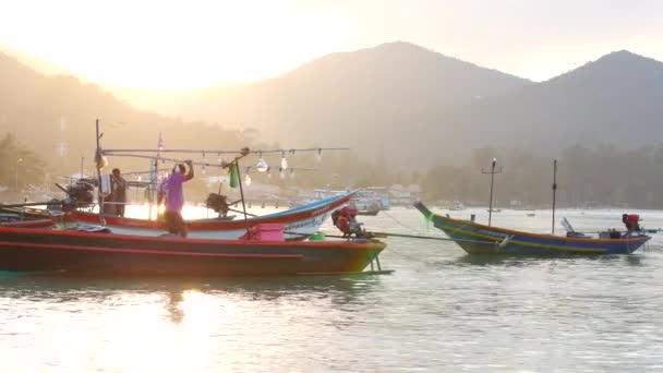 Rybářský člun se lehce houpe na vlnách v útulném zálivu