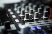 Professional party dj sound mixer controller.Focus on faders  volume regulators.Play  remix music tracks at party or concert with modern audio equipment.Sound effector close up