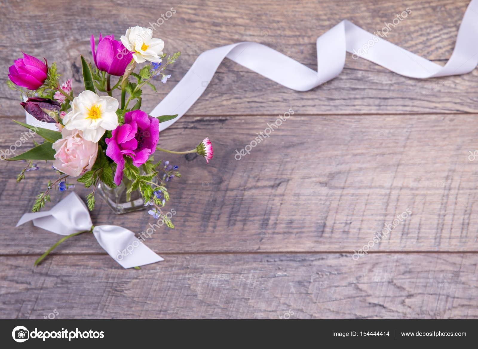 5934c9901183 Εορταστική λουλουδιών σύνθεση στο ξύλινο λευκό φόντο. Κάτοψη– εικόνα αρχείου