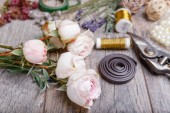 Photo Flowers, tools, ribbons, roses, lavender, herbs, greens on the florists table in flowershop. Wooden rustic style table, work space.