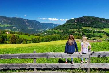 Little sisters admiring beautiful landscape