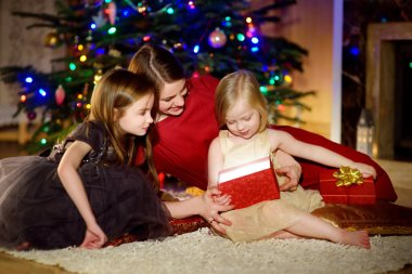 Mother and her daughters unwrapping Christmas gifts