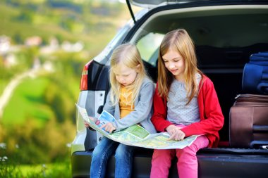Two little sisters exploring a map