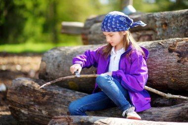 Cute little girl using a pocket knife to whittle a stick