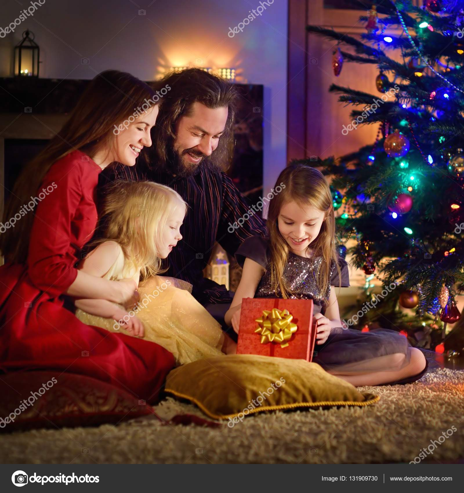 Family of four unwrapping Christmas gifts — Stock Photo © maximkabb ...