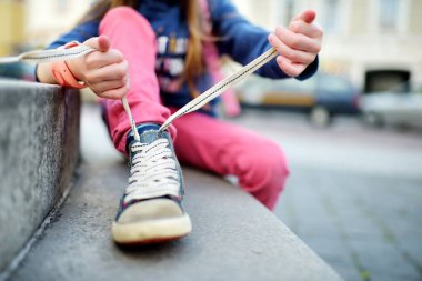 Girl learning to tie shoelaces outdoors