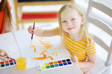 little girl drawing with colorful paints
