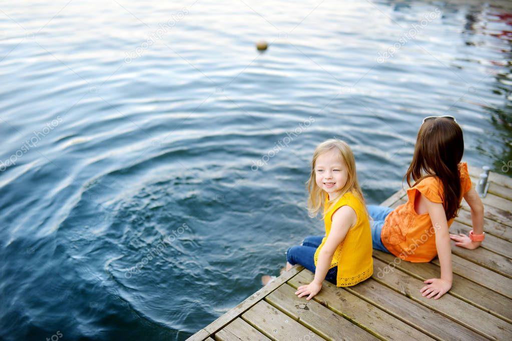 little girls sitting  near river