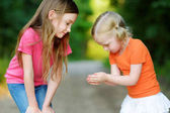Fotografie kleine Mädchen fangen Babyfrösche
