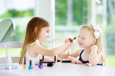Two cute funny sisters applying make-up