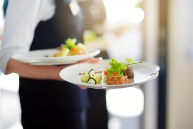 Waiter carrying plates with dishes