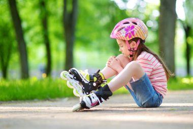 Pretty little girl learning to roller skates