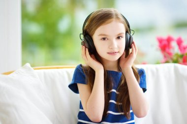 Pretty child listening to music at home
